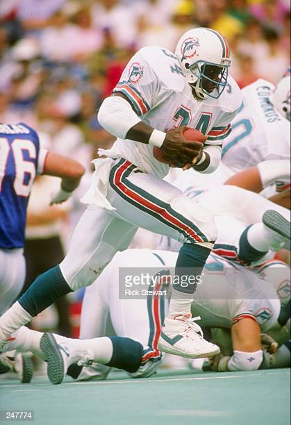 Fullback Woody Bennett of the Miami Dolphins runs with the ball during a game against the Buffalo Bills at Rich Stadium in Orchard Park, New York....