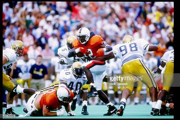 Tailback Terry Kirby of the Virginia Cavaliers tries to break a tackle during a game against the Georgia Tech Yellow Jackets at Scott Stadium in...