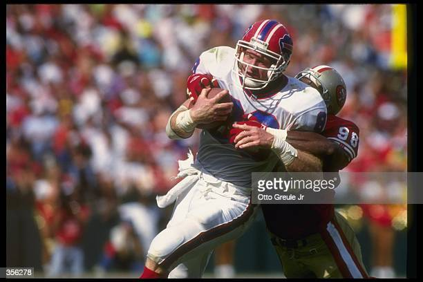 Tight end Pete Metzelaars of the Buffalo Bills gets tackled by San Francisco 49ers linebacker Antonio Goss during a game at Candlestick Park in San...