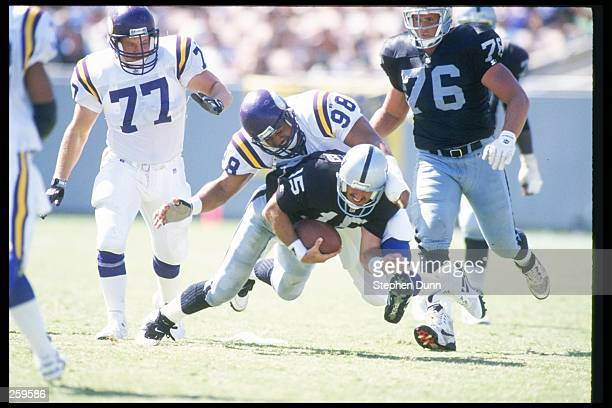 Quarterback Jeff Hostetler of the Los Angeles Raiders gets sacked by Minnesota Vikings defensive lineman Esera Tuaolo during a game at the Los...