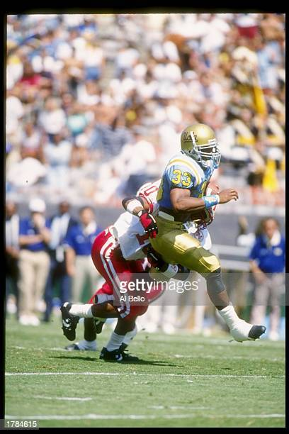 Tailback Sharmon Shah of the UCLA Bruins tries to get free of the grasp of a defensive player of the Nebraska Cornhuskers during a game at the Rose...
