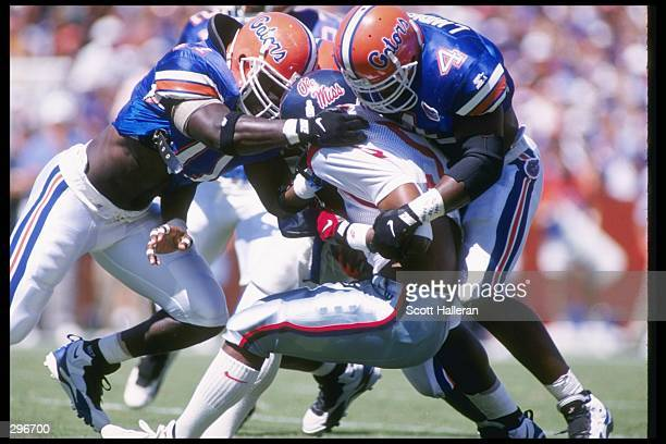 Defensive backs Lemay Thomas and Lawrence Wright of the Florida Gators make a tackle during a game against the Mississippi Rebels at Florida Field in...