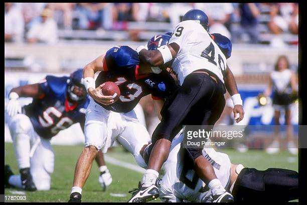Linebacker Kelvin Moses of the Wake Forest Demon Deacons tries to tackle Mike Groh of the Virginia Cavaliers during a game at Scott Stadium in...