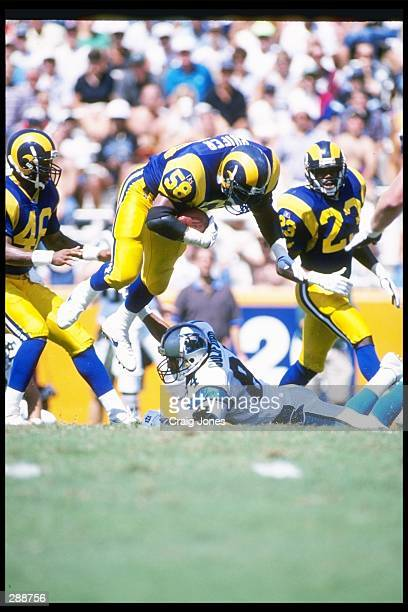 Linebacker Roman Phifer of the St. Louis Rams tackles Carolina Panthers wide receiver Eric Guliford during a game at Clemson Memorial Stadium in...