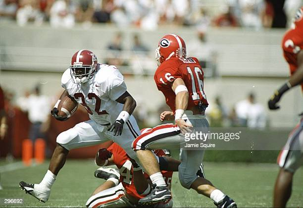 Running back Curtis Alexander of the Alabama tries to avoid defensive back Kirby Smart of the Georgia Bulldogs at Sanford Stadium in Athens Georiga...