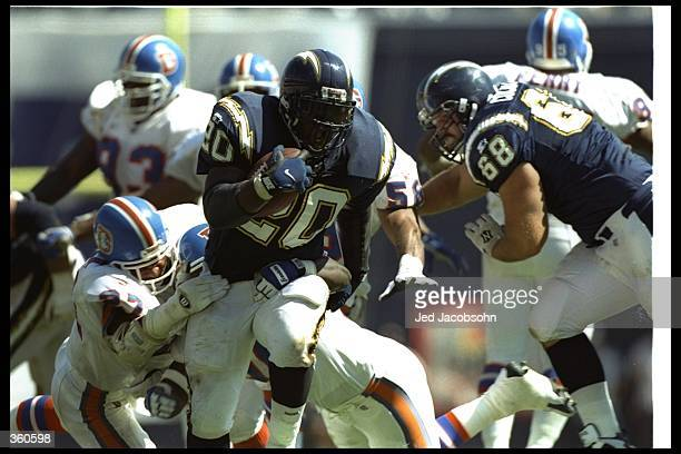 Running back Natrone Means of the San Diego Chargers moves the ball as Denver Broncos defensive back Steve Atwater attempts to tackle him during a...