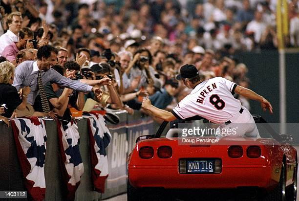 Shortstop Cal Ripken of the Baltimore Orioles shakes hands with fans at Camden Yards in Baltimore Maryland to acknowledge congratulations for...