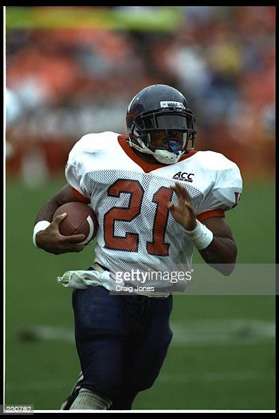Tailback Tiki Barber of the Virginia Cavaliers moves the ball against the Clemson Tigers during a game at Grant Field in Atlanta, Georgia. UVA won...