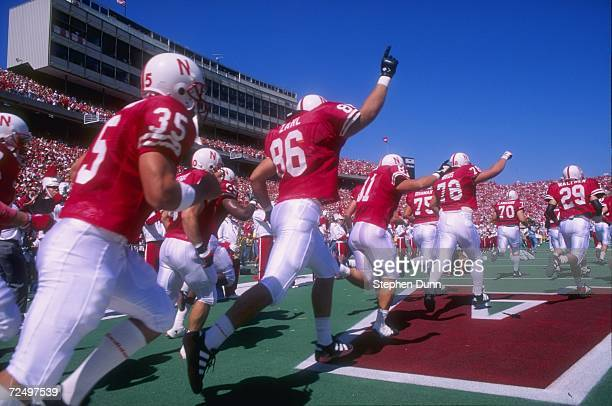 Team members from Nebraska Cornhuskers sprint onto the field during pre game intorductions as the team enters from the lockerroom just before the...