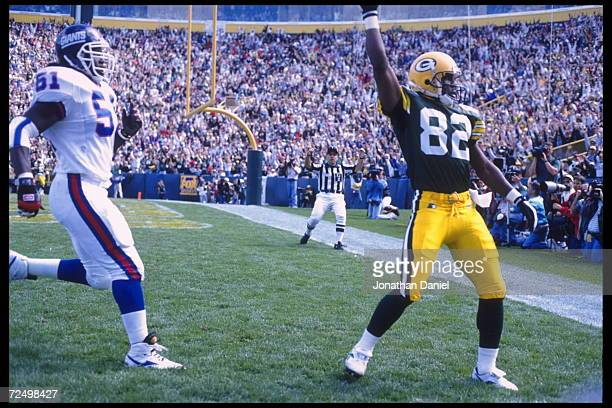 Wide receiver Mark Ingram of the Green Bay Packers holds aloft his reception in the endzone after scoring a touchdown against the New York Giants at...