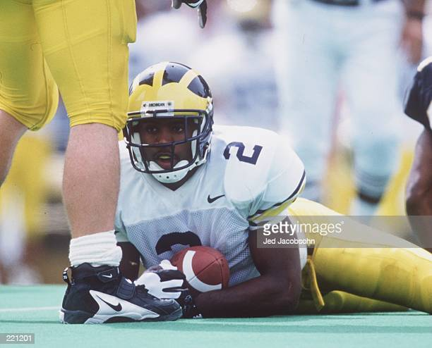 Charles Woodson of Michigan holds onto the football on the ground during their 2013 victory over Colorado at Folsom Field in Boulder Colorado