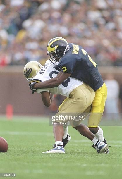 Defensive back Charles Woodson of the Michigan Wolverines tackles flanker Derek Ayers of the UCLA Bruins during a game at Michigan Stadium in Ann...