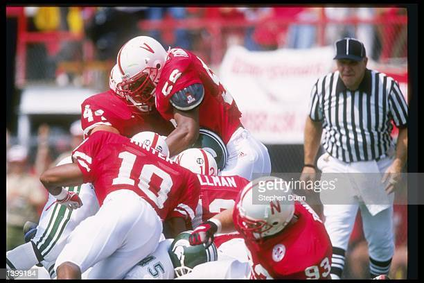Defensive back Mike Minter of the Nebraska Cornhuskers joins teammates Jason Peter Jay Foreman and Mike Fullman in a pileup during a game against the...