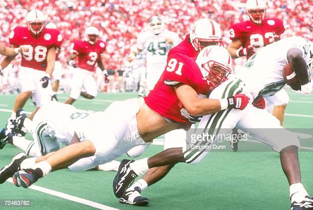 Defensive lineman Ryan Terwilliger of the Nebraska Cornhuskers leaves his feet as he dives to make a tackle in the back field on running back Nigea...