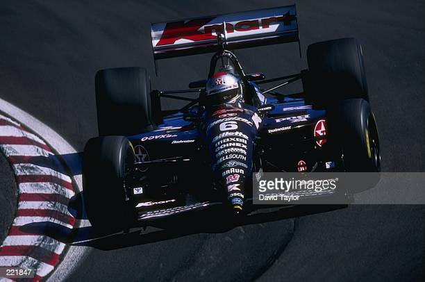 Driver Michael Andretti of the Newman Haas racing team in action on the race course as he heads into a turn while driving his Lola Ford 96 race car...