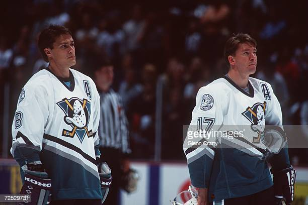 Forward Jari Kurri of the Anaheim Mighty Ducks along with teammate Teemu Selanne stand in attention as the National Anthem is played before before...