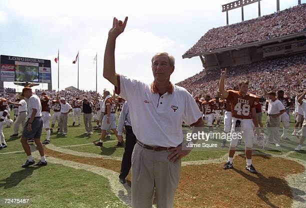 Head coach John Mackovic of the Texas Longhorns raises his hand in the air as he siganls the hook'em horns while playing the Texas anthem during the...