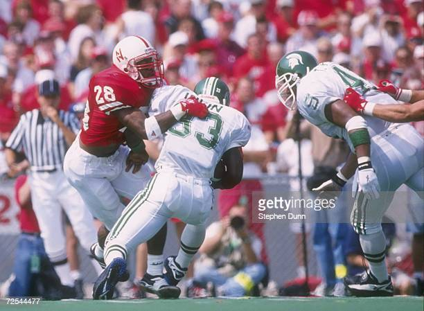 Linebacker Jamel Williams of the Nebraska Cornhuskers tackles running back Sedrick Irvin of the Michigan State Spartans during a game at Memorial...