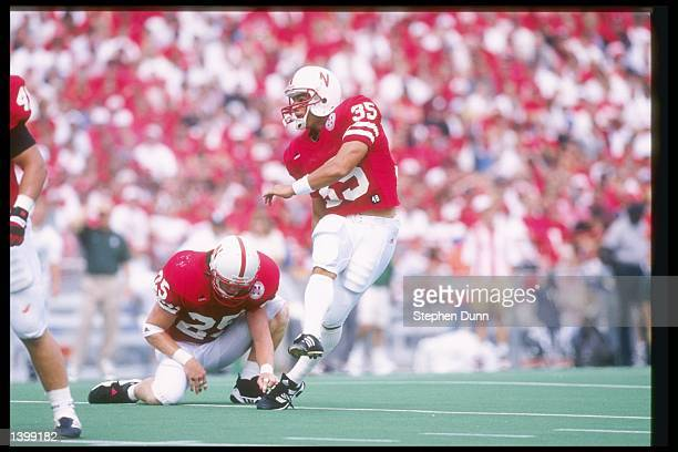 Offensive back Jon Vedral of the Nebraska Cornhuskers holds the ball as place kicker Kris Brown kicks it away during a game against the Michigan...
