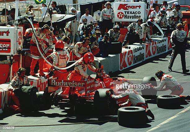 Pit crews change the tattered left rear tyre on the Newman Haas Lola Ford T96/00 of Christian Fittipaldi during the Bank of America 300 at the...