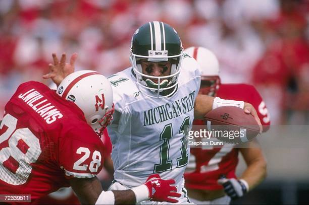 Quarterback Gus Ornstein of the Michigan State Spartans uses his right arm to fend off defensive back Jemel Williams of the Nebraska Cornhuskers as...