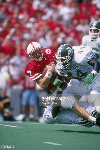 Quarterback Scott Frost of the Nebraska Cornhuskers is wrapped up and hit by a host of defenders from the Michigan State Spartans lead by Ike Reese...