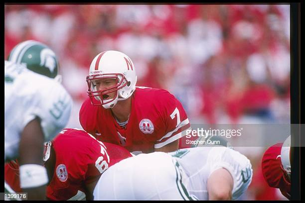 Quarterback Scott Frost of the Nebraska Cornhuskers prepares to take the snap from center Aaron Taylor during a game against the Michigan State...