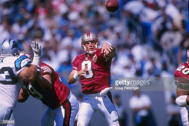 Quarterback Steve Young of the San Francisco 49ers releases the football as he follows through on a pass while looking down field at his open...