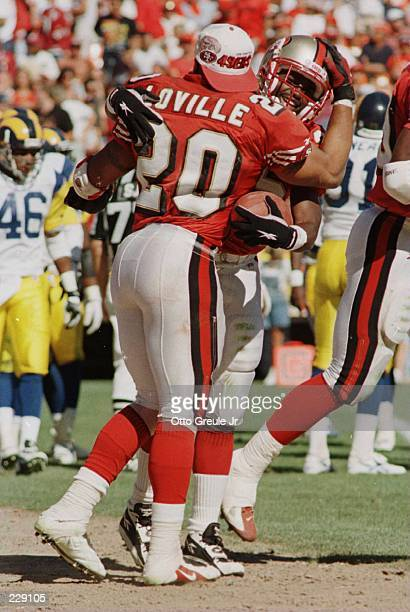 Running back Dexter Carter of the San Francisco 49ers celebrates with teammate Derek Loville after scoring the last touchdown during the 49ers 340...