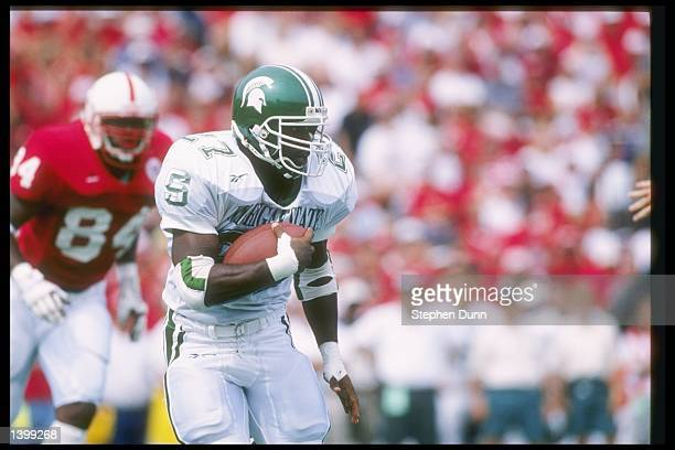 Running back Duane Goldbourne of the Michigan State Spartans runs down the field as Mike Rucker of the Nebraska Cornhuskers chases after him at...