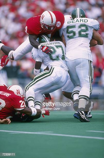 Running back Duane Goulabourne of the Michigan State Spartans is hit high and low by a host of defenders lead by Octavious McFarlin of the Nebraska...