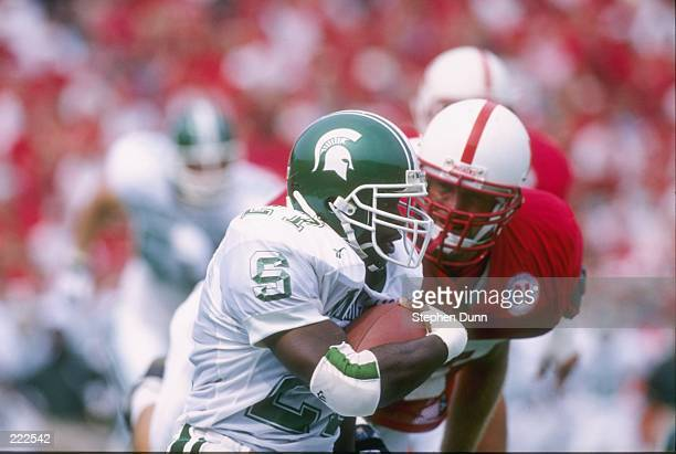 Running back Duane Goulbourne of the Michigan State Spartans looks up field as he makes a cut to the outside to avoid a pursuing defender from the...