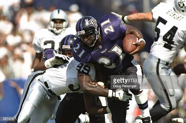Running back Earnest Byner of the Baltimore Ravens uses his right arm in attempts to fight through the tackle of defensive lineman Aundray Bruce of...
