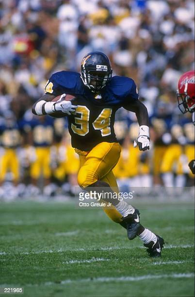 Running back Tarik Smith of the Cal Golden Bears looks up field at a pursuing defender from the San Diego State Aztecs as he makes a cut to the...