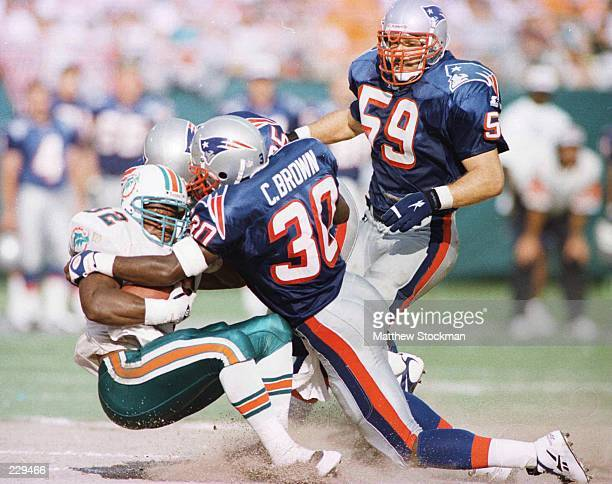Runningback Jerris McPhail of Miami is brought down byCorwin Brown Larry Whigham and Todd Collins of New England at Pro Player Park in Miami Florida...