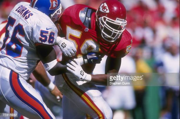 Special teams player Donnie Edwards of the Kansas City Chiefs attempts to run through the block of Keith Burns of the Denver Broncos while pursuing...