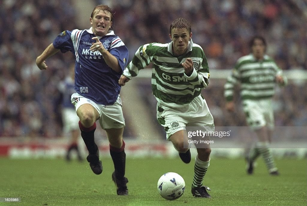 Stuart McCall (left)of Glasgow Rangers and Simon Donnelly (right) of  Celtic running after the ball : News Photo