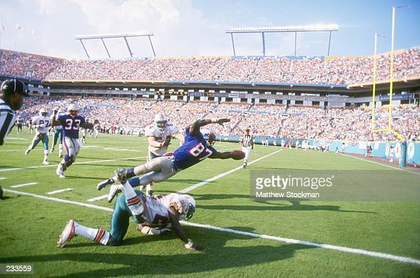 Tight end Ben Coates of the New England Patriots leaves his feet as he lunges across the goal line for a touch down while linebacker Zach Thomas of...