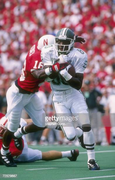 Wide receiver Derrick Mason of the Michigan State Spartans attempts to break free from the grasp of defensive back Eric Stokes of the Nebraska...