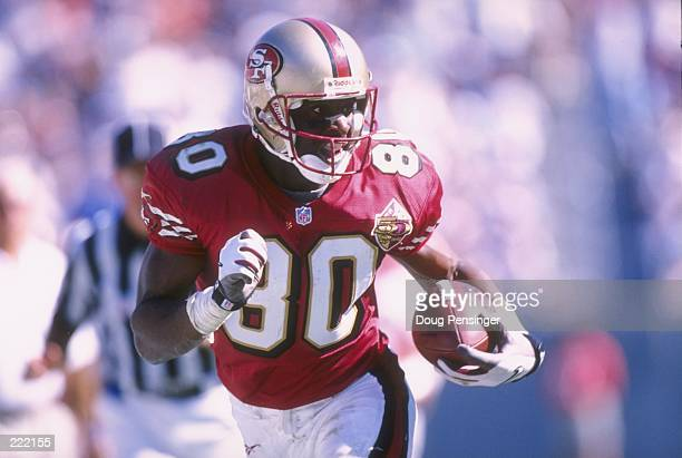 Wide receiver Jerry Rice of the San Francisco 49ers keep his eyes focused up field as he makes a cut to the sideline while running with the football...