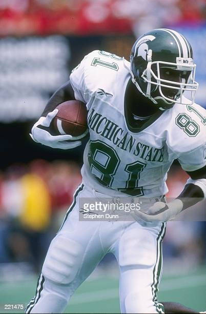 Wide receiver Nigea Carter of the Michigan State Spartans looks up field as he scans the defense while running with the football following a...