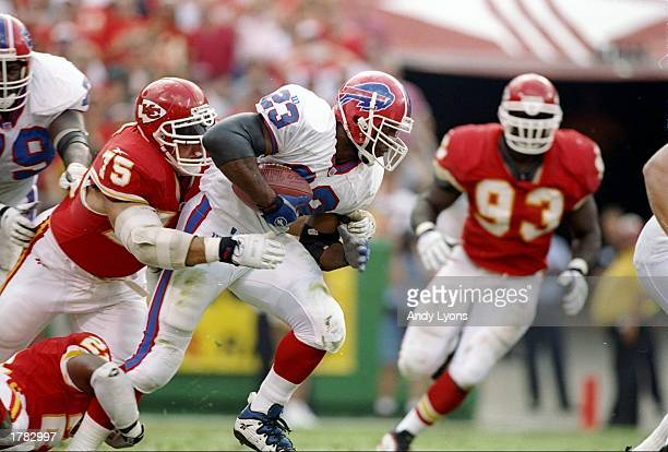 Defensive tackle Joe Phillips of the Kansas City Chiefs tries to tackle Antowain Smith of the Buffalo Bills during a game at Arrowhead Stadium in...
