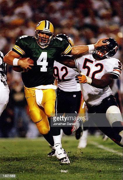 Quarterback Brett Favre of the Green Bay gives a stiff arm to linebacker Bryan Cox of the Bears during the Packers 3824 win over the Chicago Bears at...