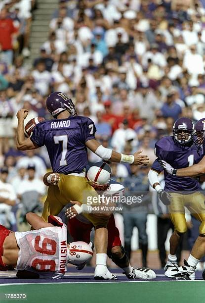 Quarterback Brock Huard of the Washington Huskies gets hit by defensive linemen Grant Wistrom and Jason Peter of the Nebraska Cornhuskers during a...