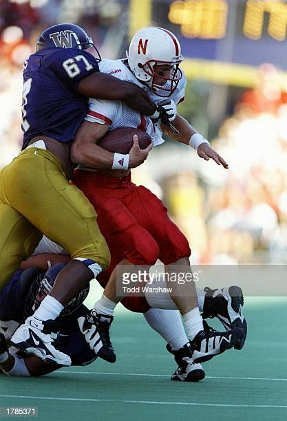 Quarterback Scott Frost of the Nebraska Cornhuskers gets hit by defensive lineman Sekou Wiggs of the Washington Huskies during a game at Husky...