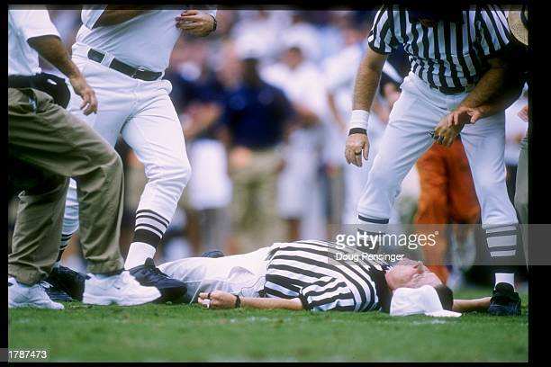 Referee James Knight lays on the ground after suffering a massive heart attack during a game between the Virginia Cavaliers and the North Carolina...