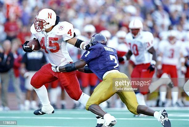 Running back Joel Makovicka of the Nebraska Cornhuskers moves the ball as defensive back Tony Parrish of the Washington Huskies chases him during a...