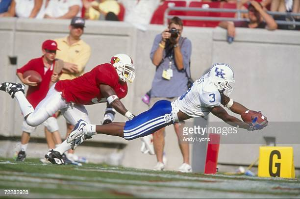 Craig Yeast of the Kentucky Wildcats dives across the goal line while being pursued by a member of the Louisville Cardinals during a game at the Papa...