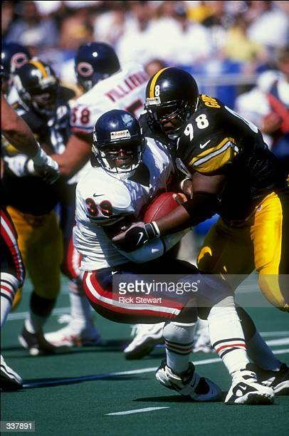 Defensive Tackle Oliver Gibson of the Pittsburgh Steelers tackling Curtis Enis during the game against the Chicago Bears at the 3 Rivers Stadium in...