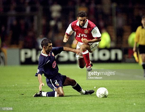 Eric Sikora of Arsenal is tackled during the UEFA Champions League against Lens at the Felix Bollarent Stadium in Lens France The game ended in a...